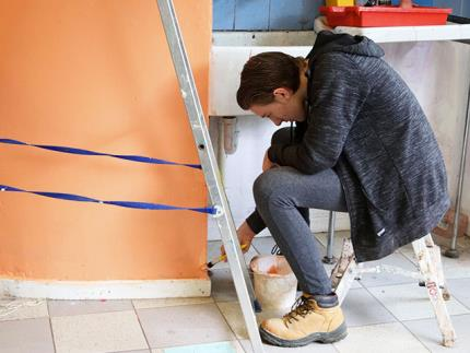 Student sitting on a small step ladder painting a wall with a brush