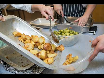 Roast potatoes being tipped into a bowl