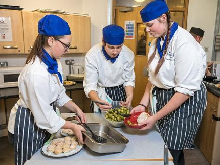 Three Highbury students preparing Christmas dinner at Hope House homeless shelter kitchen
