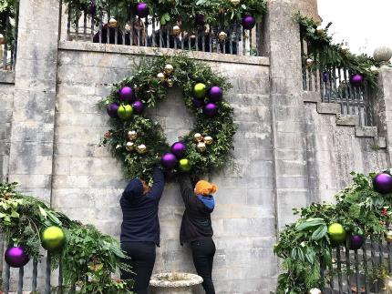 Highbury College floristry students hanging a Christmas Wreath at Mottisfont