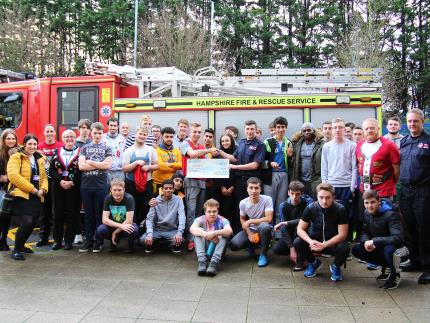 Highbury College students presented a cheque to Cosham firefighters in front of fire engine