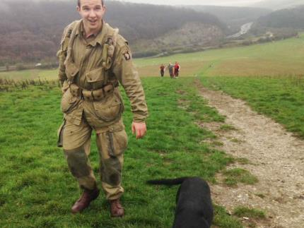 Public services student in WWII soldier dress running up Butser Hill with a dog