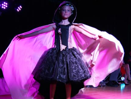 A child model in a fashion show wearing a puffy dress with a cape flaring out behind her