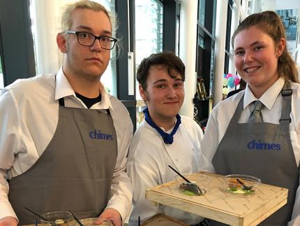 Three student chefs holding hors d'oeuvres on wooden trays