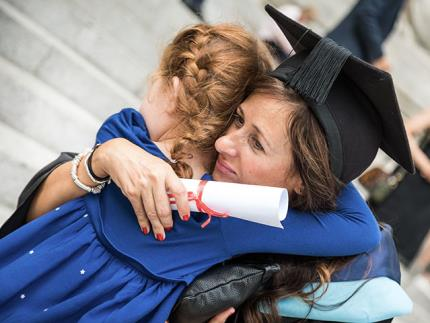 A graduate in academic robes hugging her child outside the guildhall