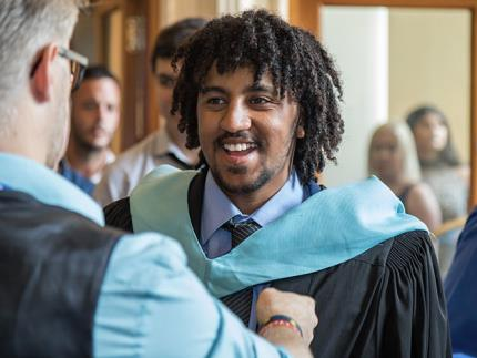 Smiling student being fitted with an academic gown at graduation