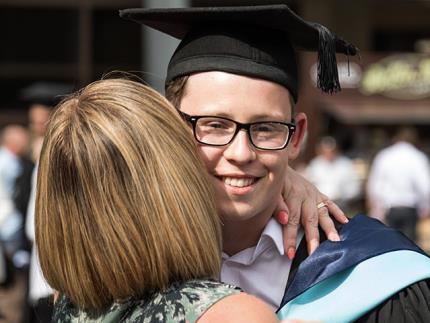 A close up of a male student in academic robes being hugged by a loved one
