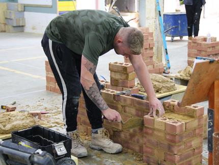 A student carefully  laying a brick in a workshop