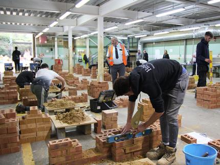 Bricklaying students building walls in a workshop while an assessor walks through