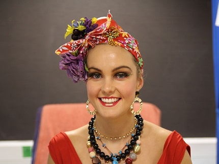 Smiling make-up model with Carmen Miranda fruit hat and bold chunky costume jewellery