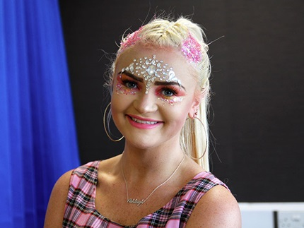Make-up smiling at camera with festival face jewels and hair glitter