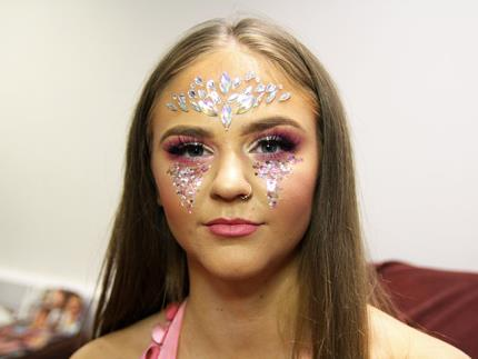 Make-up smiling at camera with festival face jewels