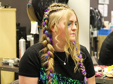 Angled profile of hair model with multi-coloured braids and hair glitter
