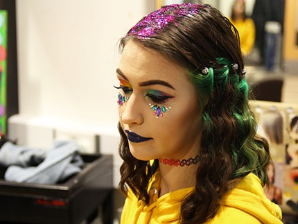 Angled profile of hair model with hair glitter at  crown of head, loose multi-coloured curls and rainbow make-up and face jewels