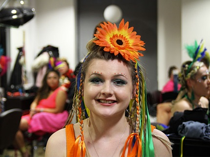 Smiling hair model with braids, ribbons and a large orange sunflower hair accessory