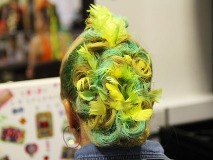Back of hair model's head with messy multi-coloured bun and feather accessories