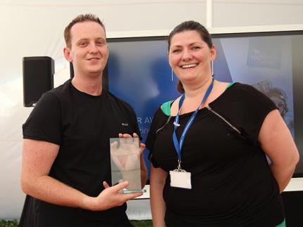 Staff member accepting an engraved glass award from another staff member
