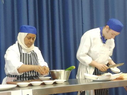 Two culinary students chopping vegetables at a competition