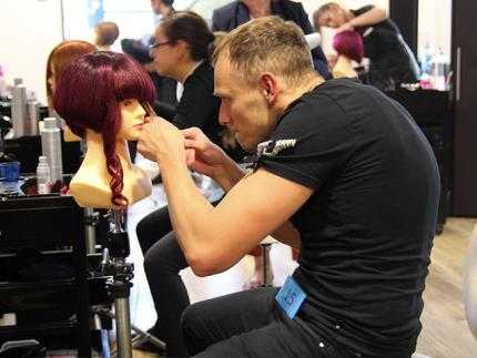 Male hairdressing student cutting mannequin hair