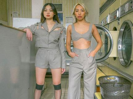 Two models in a laundrette wearing Cabrini Roy clothes