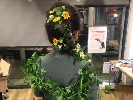 Back of hair model's head with fake ivy and flowers pinned in