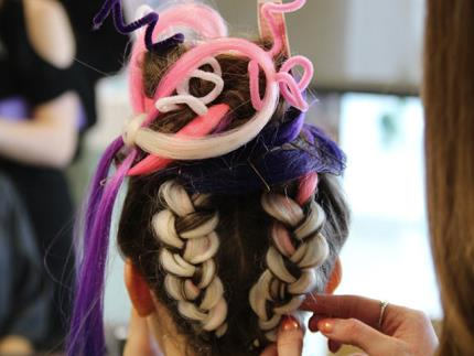 Back of model's head with hairdresser adjusting braid in multicoloured hairstyle