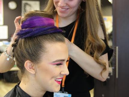 Side profile of smiling hair model with hairdresser pinning multicoloured bun