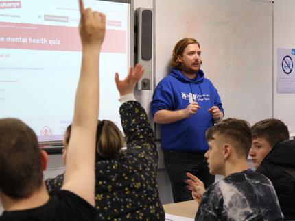 Male mental health charity Mind volunteer at the front of a classroom with students' hands up in the air