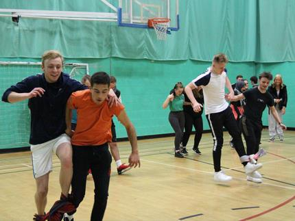 Students running in pairs in a three-legged race in a sports hall