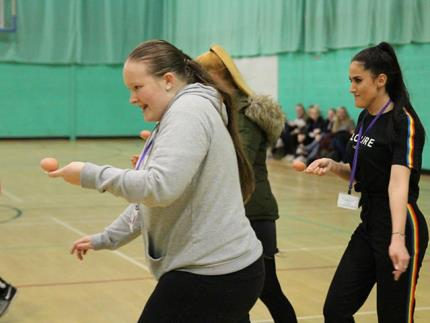 Students running in an egg and spoon race in a sports hall