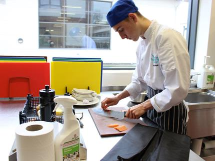 Male catering student cutting carrots in a commercial kitchen