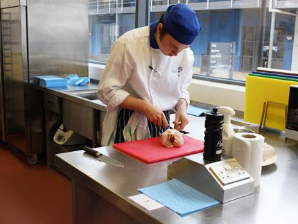 Male catering student preparing a chicken in a commercial kitchen