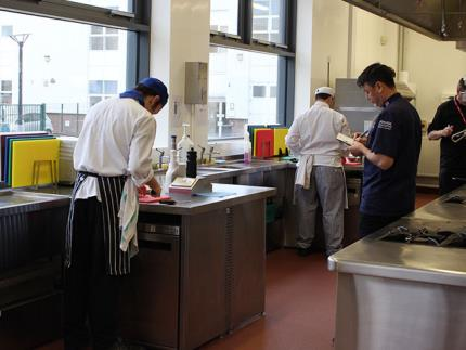 Catering assessors looking over students in a commercial kitchen