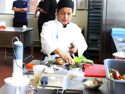 Female catering student looking over vegetables in a commercial kitchen