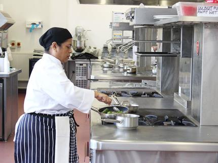 A female catering student cooking over a hob in a commercial kitchen