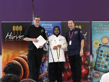 A female catering student receiving a medal at a podium with two male judges either side