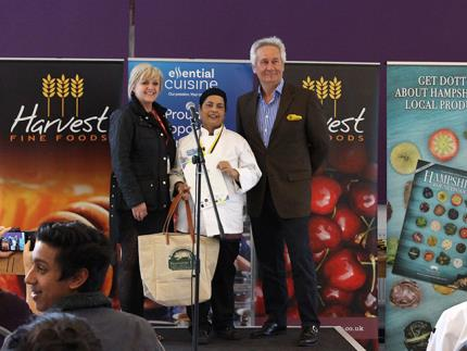 A female catering student receiving an award and a Hampshire Fare goodie bag at a podium with a female and male judge either side