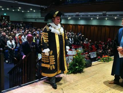 Lord Mayor of Portsmouth Councillor Lee Mason walking up the steps to the stage at the mayor-making ceremony