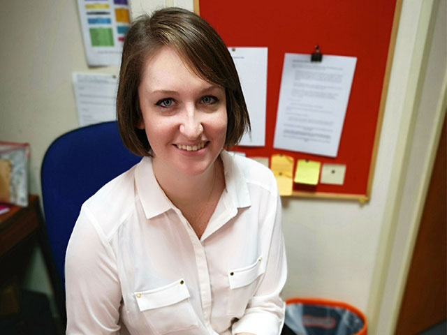 Highbury apprentice Megan at her desk in an office