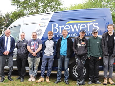 Brewers representatives standing with Highbury College students and Paulsgrove Adventure Playground representative in front of a Brewers van