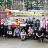 A cheque presentation from Highbury College students to firefighters from Cosham Fire Station in front of a fire engine