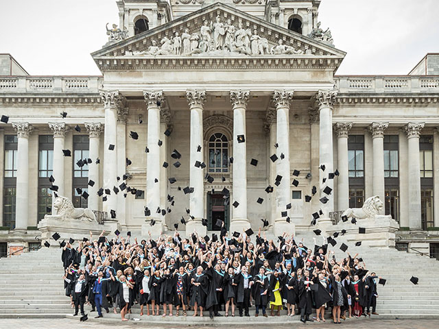 Students throwing their mortarboards into the air on Portsmouth Guildhall steps