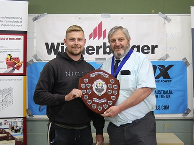 Highbury student Ben receiving a plaque from a member of the Guild of Bricklayers