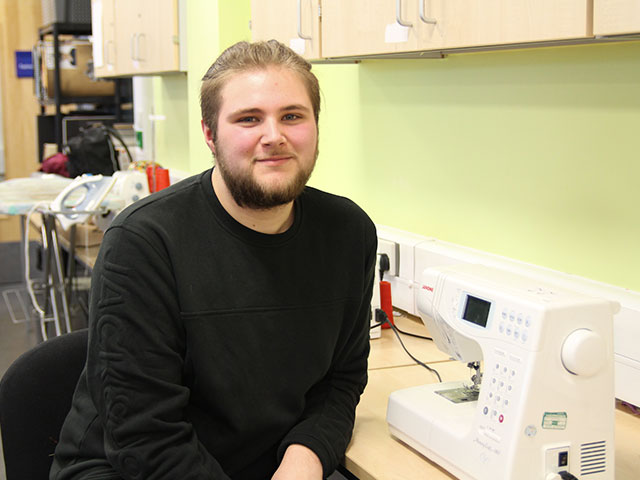 Former Highbury College student Michael Rixon sitting in a classroom next to a sewing machine