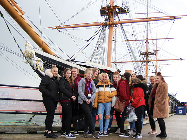 A group of students standing on a pier in front of a historic ship on a rainy day