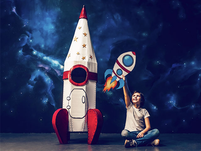 Boy sitting near toy rocket on space background with drawn small rocket in hand.