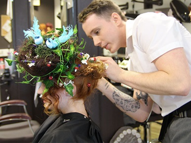 Hairdresser working on model's elaborate hairstyle styled as a colourful bird's nest