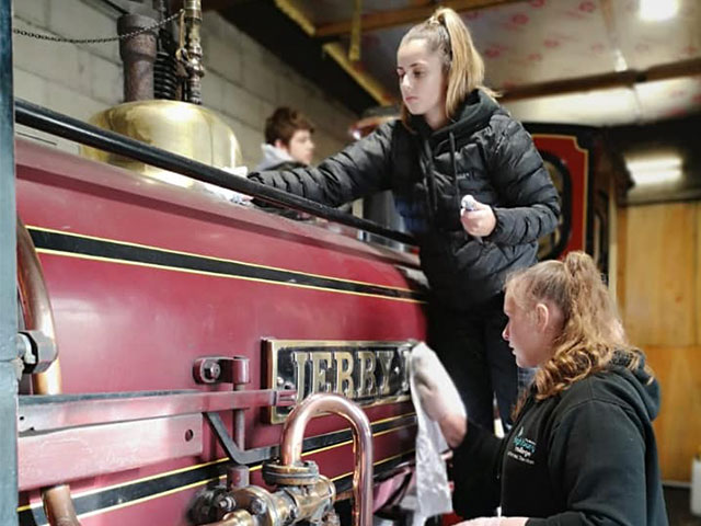 Two teen students cleaning a red steam locomotive called Jerry M