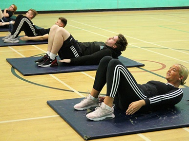 Highbury College Public Services's students working out on mats