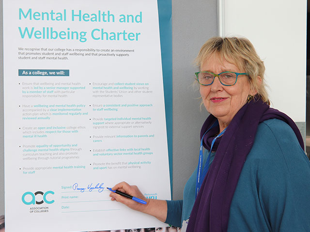 Principal Penny Wycherley signing the AoC Mental Health Charter